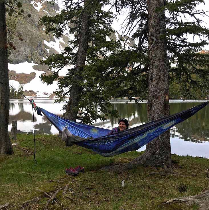 girl sitting and smiling in a blue hammock by a lake