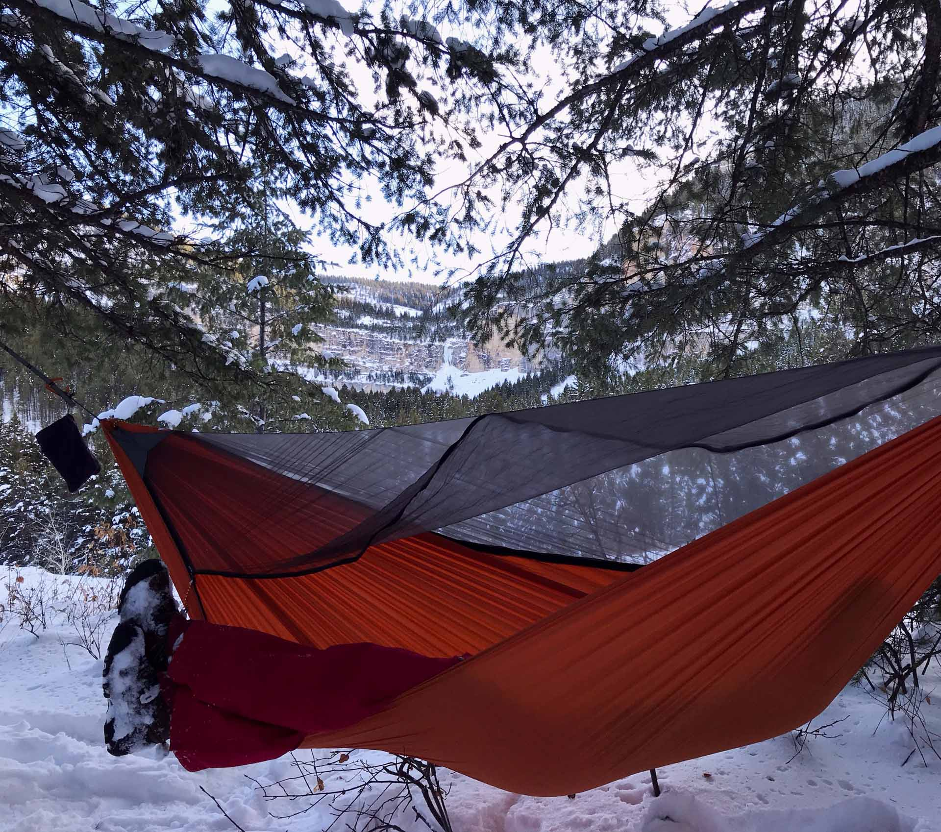 orange hammock camping gear with bug net set-up above the winter snow