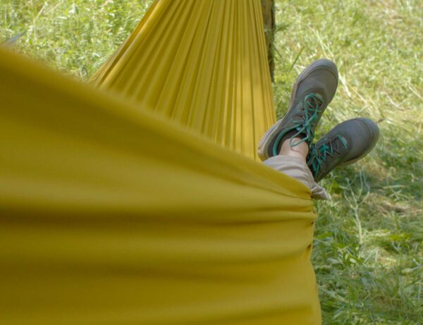 feet with hiking shoes outside of a yellow hammock
