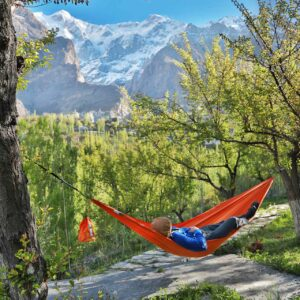 a red hammock set up between 2 trees with a person resting,